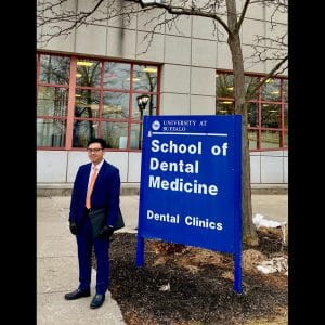 Andy Le stands in front of the University of Buffalo School of Dental Medicine sign