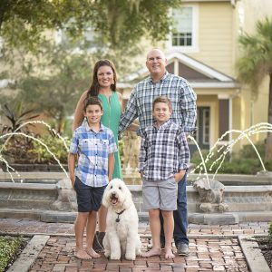 Cindy Trautmann poses with her husband, two sons and dog in front of a fountain, garden and yellow house