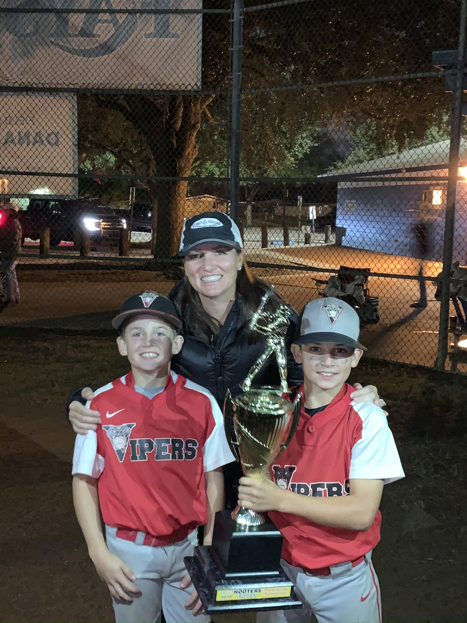Cindy Trautmann with her sons CJ and Josh in baseball uniforms holding a trophy.