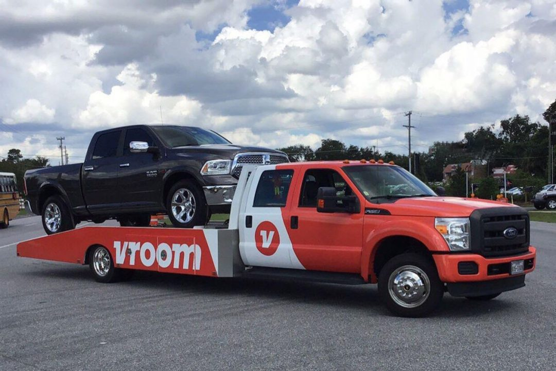 A red flatbed tow truck with a large black truck being towed.