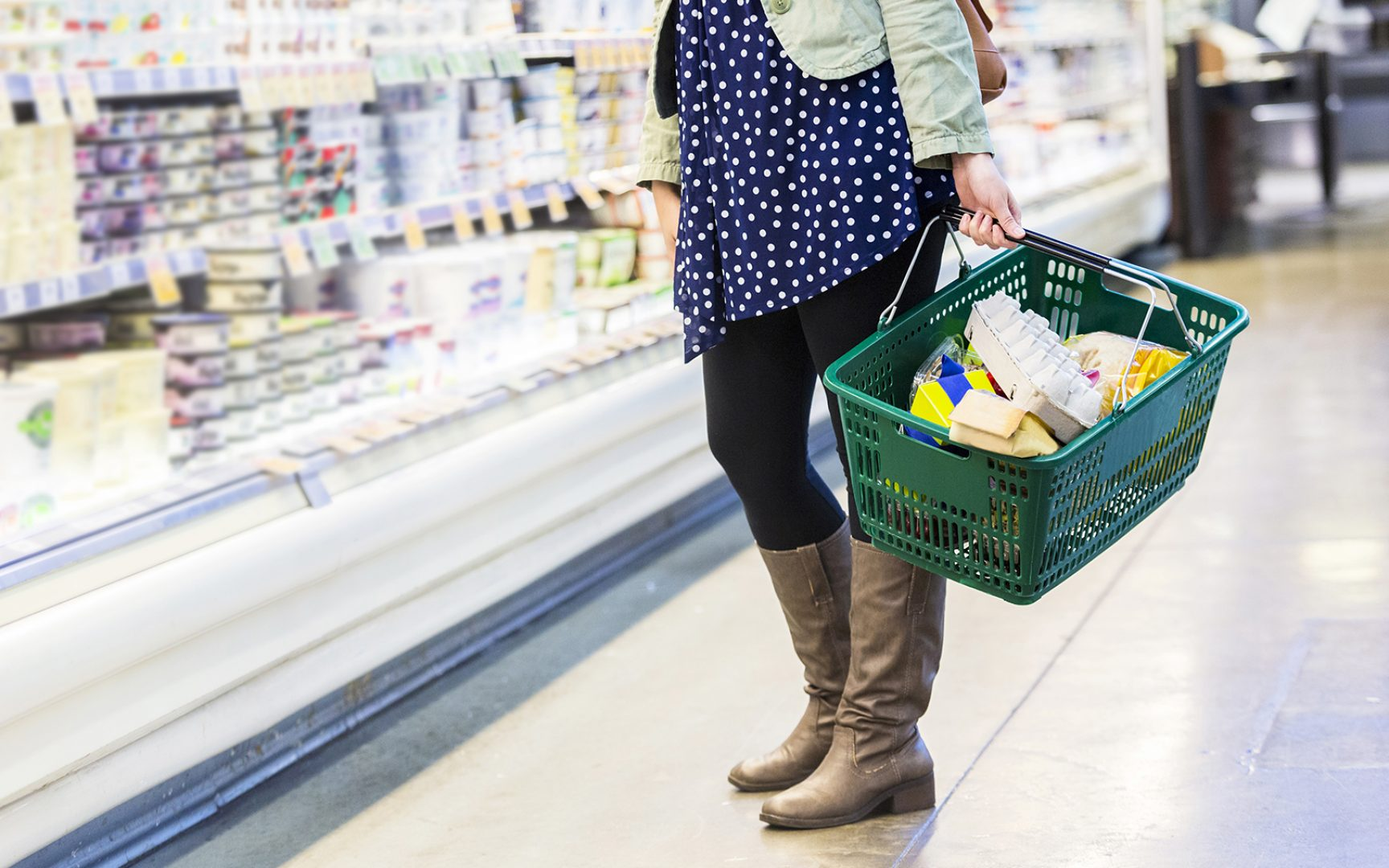Lower half of a woman grocery shopping, she is holding a green shopping basket.