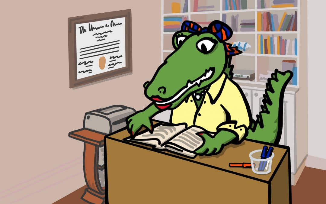 Cartoon Alberta Gator sitting at a desk reading a book. Her UF degree hangs on the wall to her right and a bookshelf filled with books is behind her.