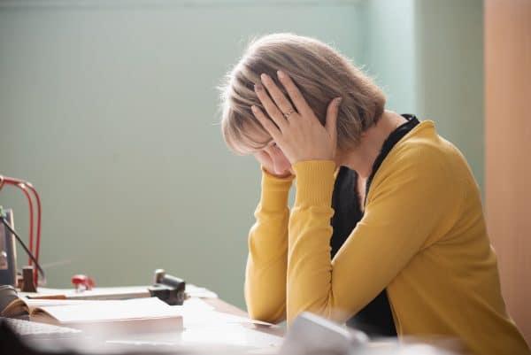 Overworked teacher is sitting by her desk.