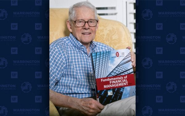 Eugene Brigham sits in a chair holding a copy of his textbook Fundamentals of Financial Management