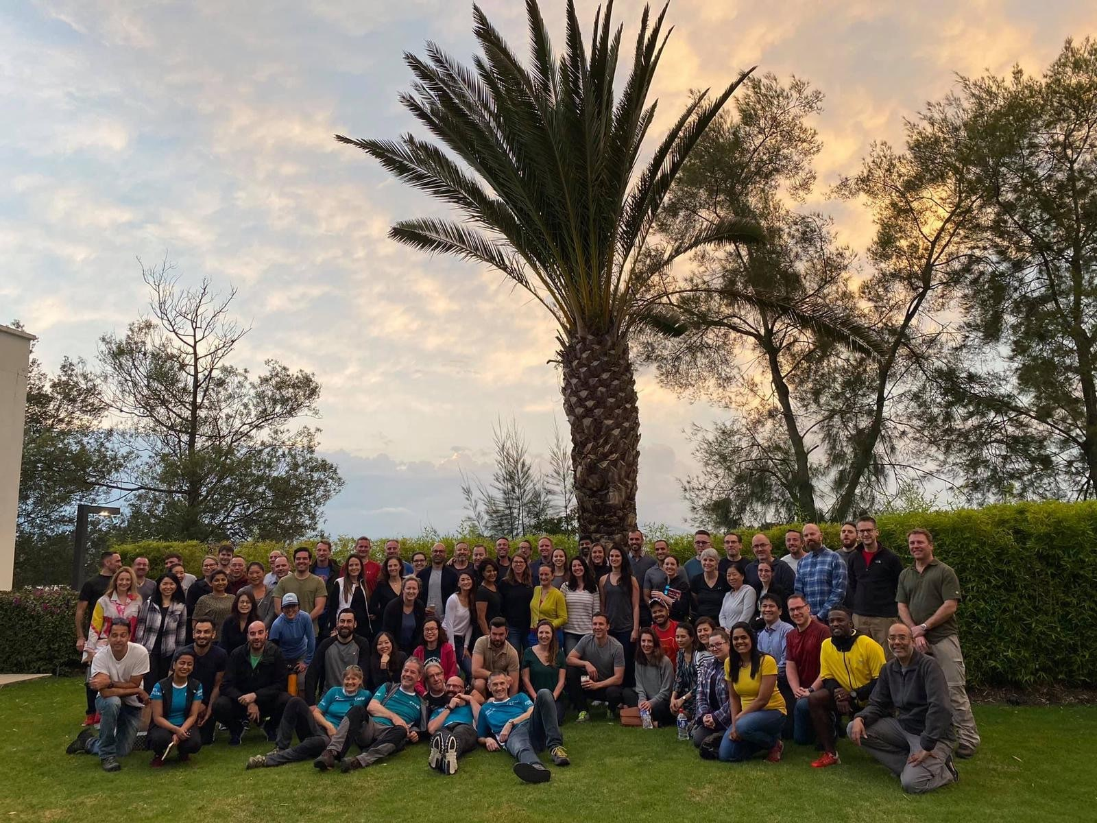 A group of about 80 people pose for a group photo in front of a palm tree.