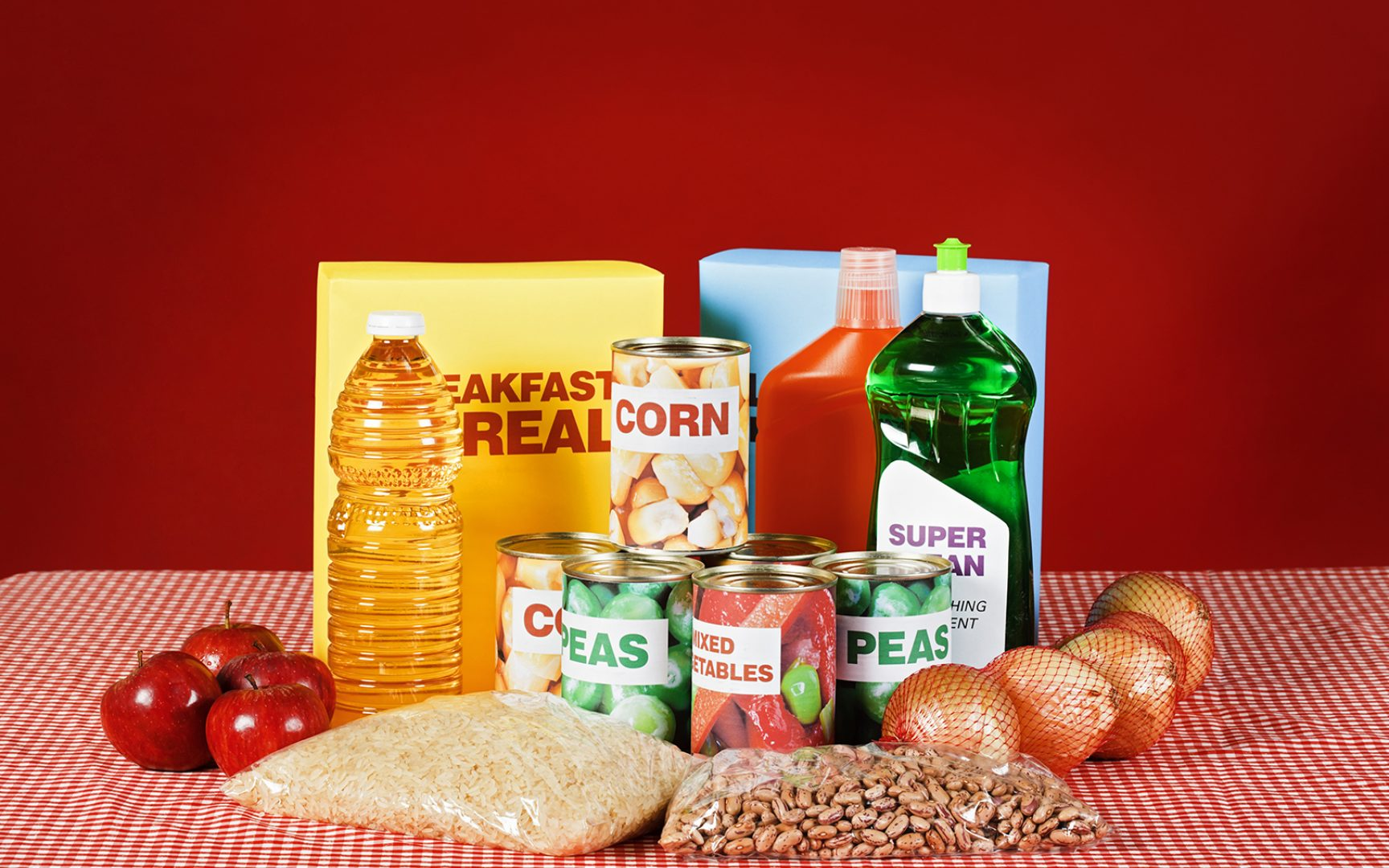 Generic food and cleaning products on gingham against red.