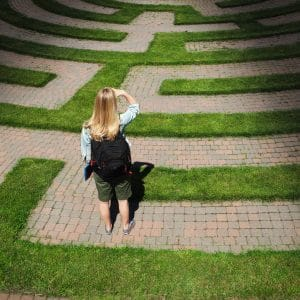 A woman student stands looking through the puzzling maze of schooling and the education system, forecasting the way forward and searching for the path to her goal. Concept of student facing uncertainty to their education, life and future career.