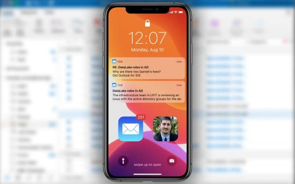 Blurred Microsoft Outlook email background with an iPhone in the foreground that has two Outlook email notifications and a photo of James Martinez