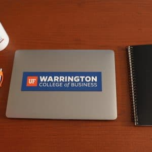 Birds eye view of a lap top with a Warrington sticker, notebook, pen, cell phone and coffee mug with a hand on the handle.