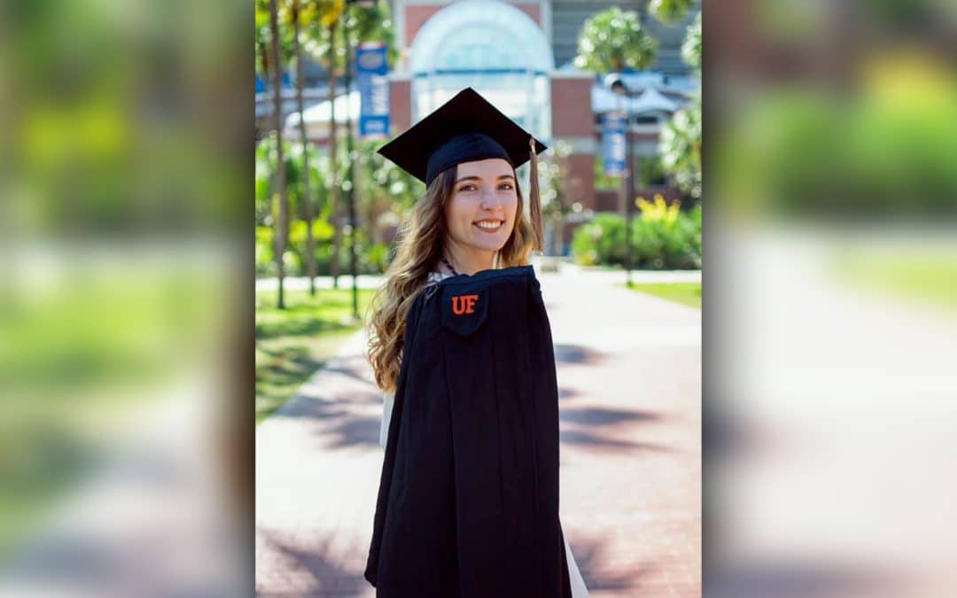 Leia Wojciechowski wearing a cap and gown in front of Ben Hill Griffin Stadium