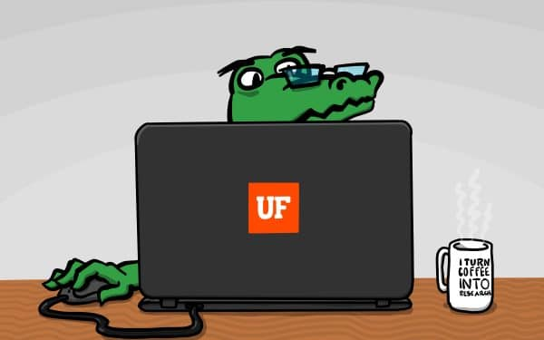 Cartoon alligator sitting at a computer. He wears glasses and is using a mouse to navigate on the computer. He has a UF logo sticker on his computer and a coffee mug next to his computer that reads I turn coffee into research.
