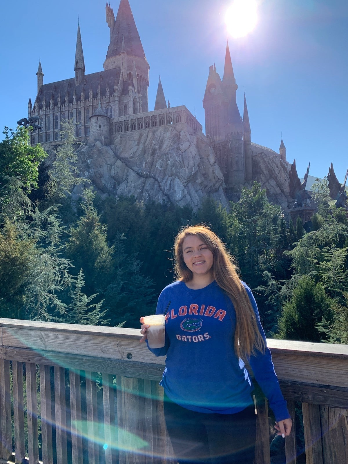 Monique Atkinson poses in front of the Hogwartz Castle at Harry Potter World at Universal Orlando. She wears a blue Florida Gators shirt and holds a butter beer.