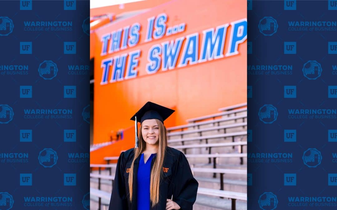 Monique Atkinson poses for a photo in a graduation cap and gown in the Swamp. Text behind her reads This is...The Swamp.