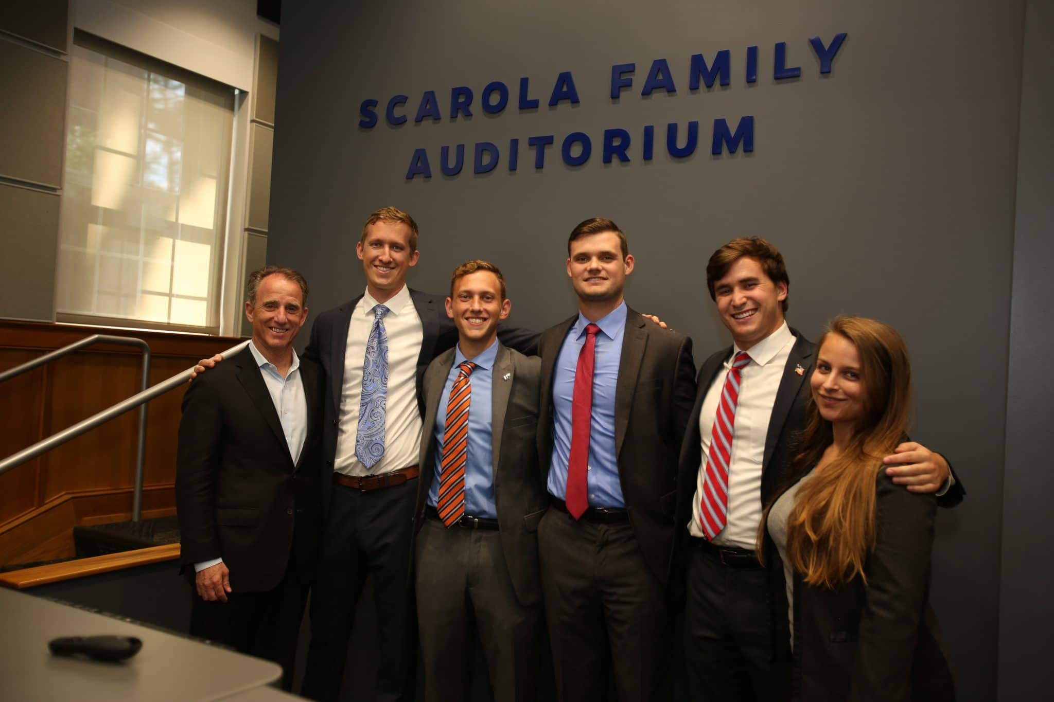 Rick Scarola with five students posing for a photo in front of the Scarola Family Auditorium sign