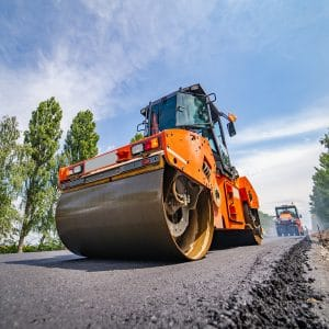 Road repair, compactor lays asphalt. Heavy special machines. Asphalt paver in operation. Side view. Closeup.