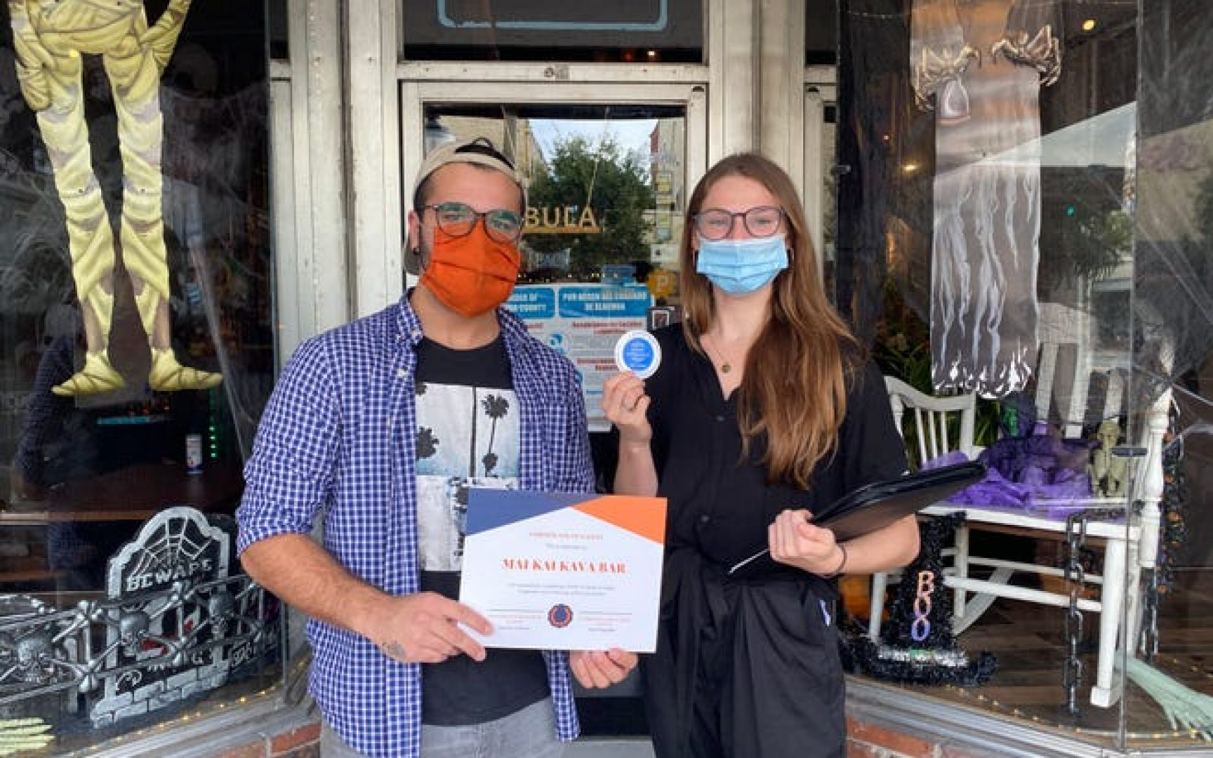 Two people stand in a doorway. Both wear masks as one holds up a certificate and the other holds a sticker.