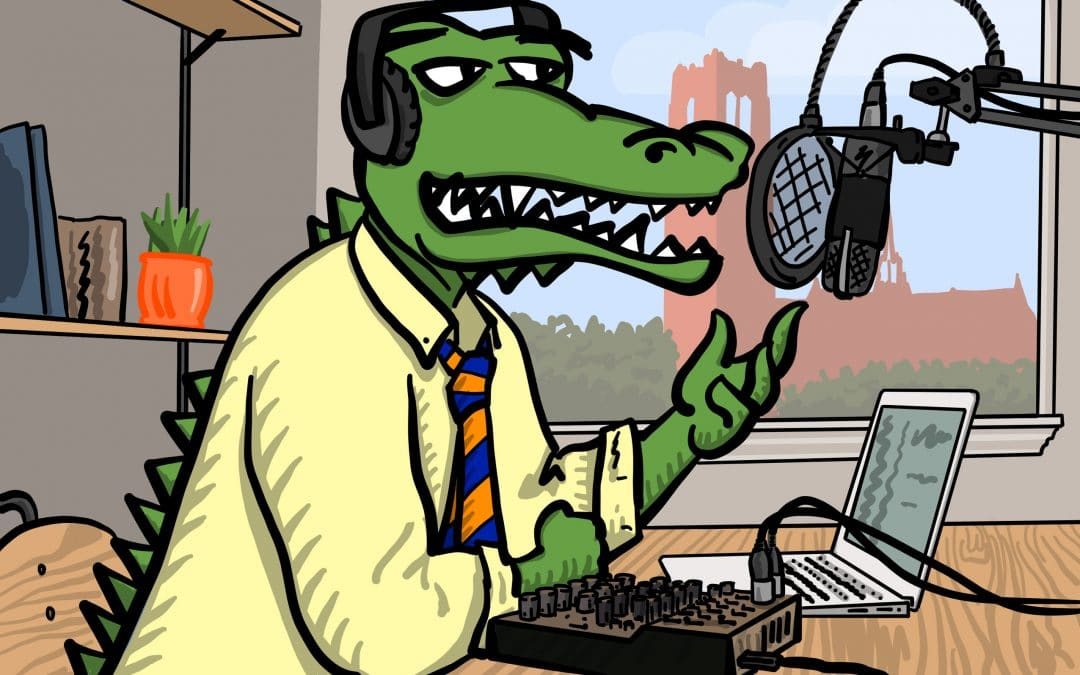 Albert Gator wearing a yellow shirt and orange and blue tie speaking into a microphone and wearing headphones while recording a podcast. Century Tower is in a window behind him.