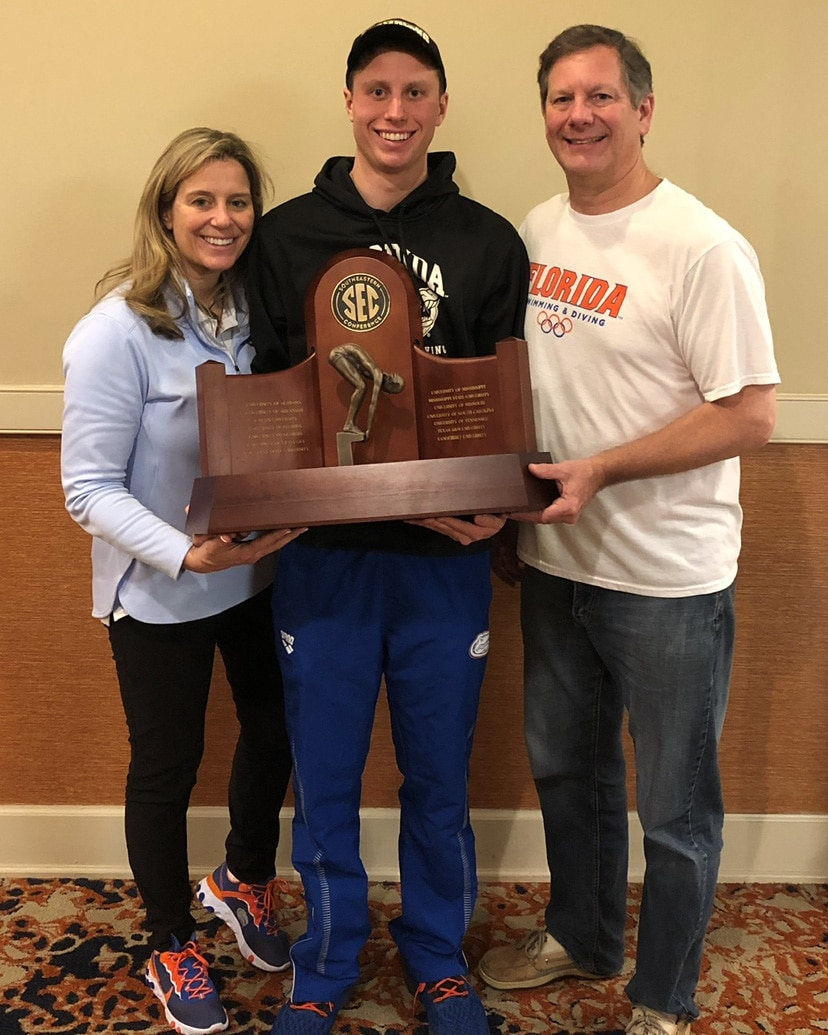 Matthew Anderson (center) holding an SEC Swimming trophy with his mom on his right and dad on his left.