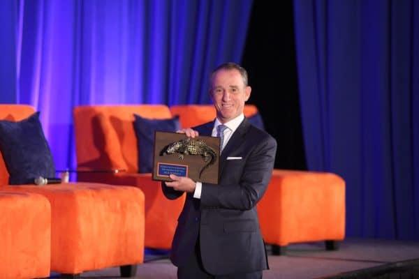 Rick Scarola holds his 2016 Bergstrom Center Alumnus of the Year award