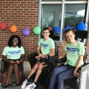 """Three wheelchair-using UF students pose for a photo wearing shirts that say """"The future is accessible"""""""