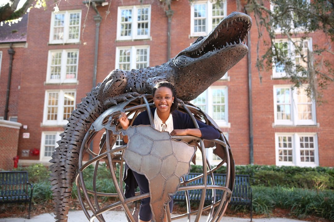 Rachelle Antoine stands inside the globe of the Gator Ubiquity Statue