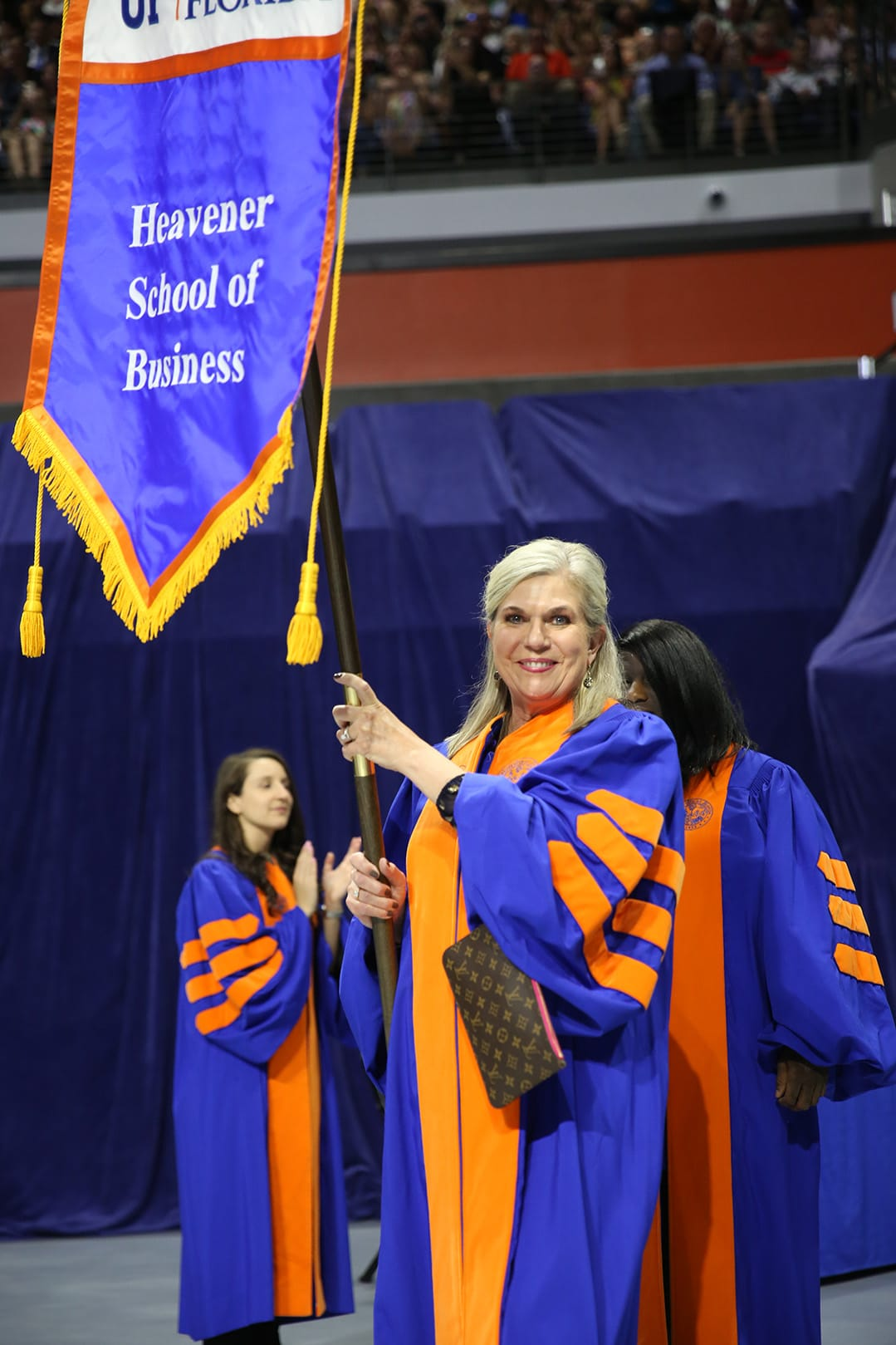 Betsy Goodman holds the Heavener School of Business flag at Commencement
