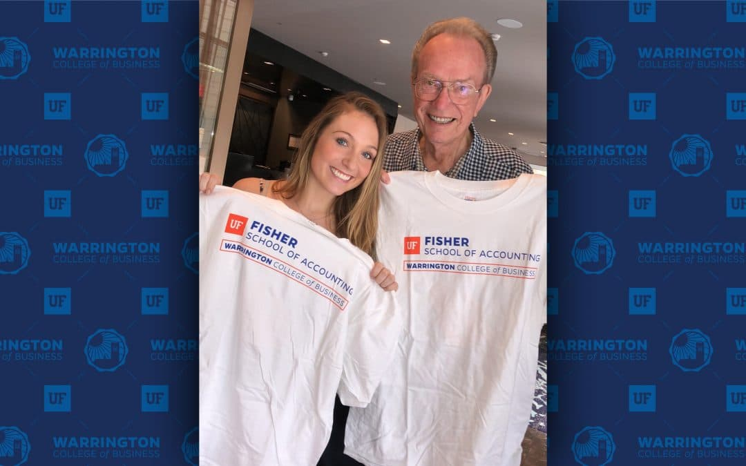 Quinn Fisher Simpson and Fred Fisher hold up t-shirts that read Fisher School of Accounting