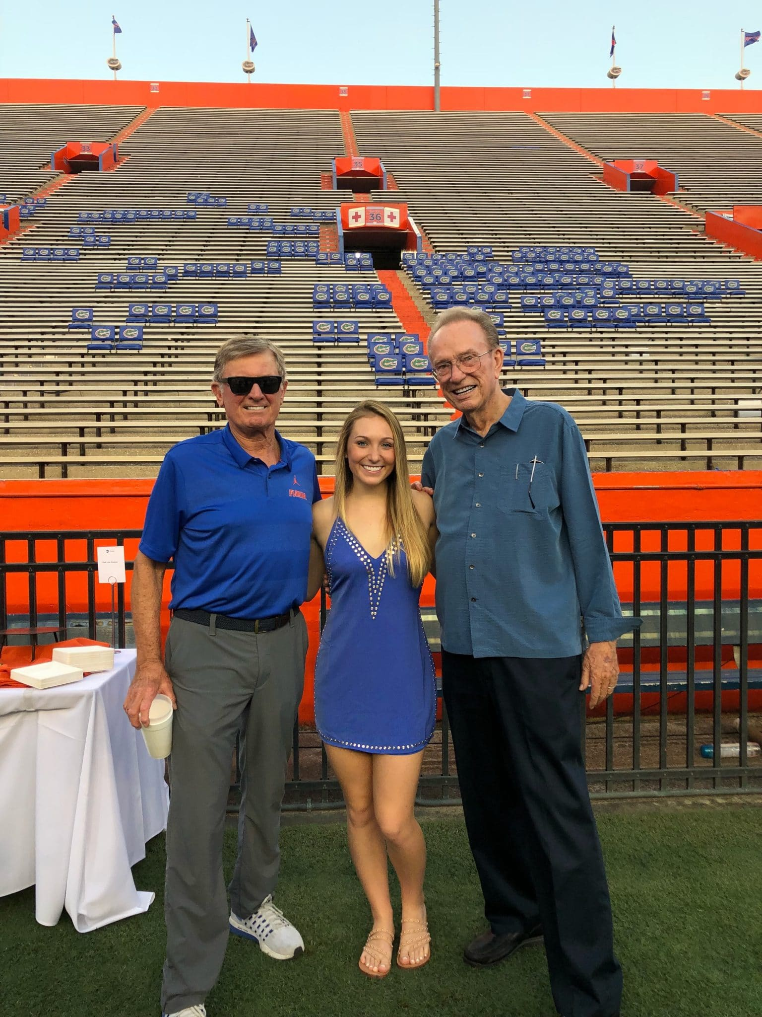 Steve Spurrier, Quinn Fisher Simpson and Fred Fisher pose for a photo in Ben Hill Griffin Stadium