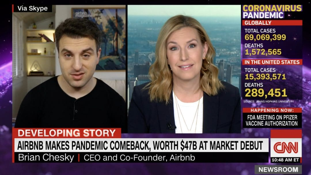Airbnb CEO speaks on screen with CNN reporter about the company's IPO