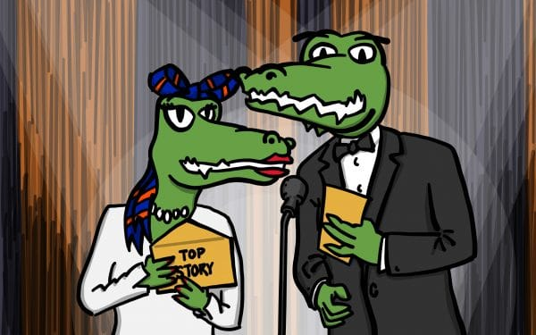 """Alberta and Albert Gator stand in front of a microphone on a stage presenting the """"top story"""" at Warrington. They hold envelopes with """"top story"""" written on the front."""