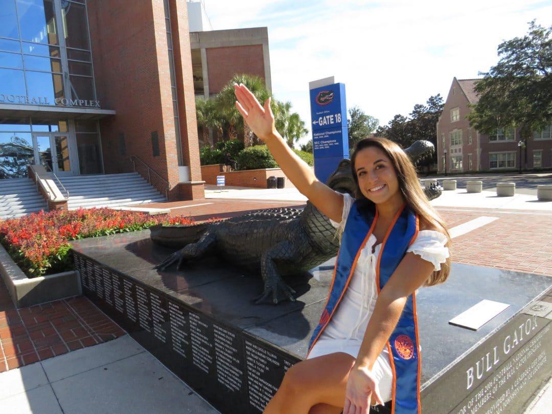 Alyssa Miranda does the Gator Chomp in front of the Gator Statue