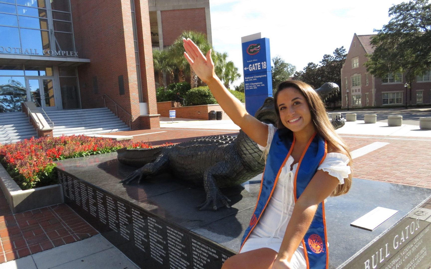 Alyssa Miranda does the Gator Chomp in front of the Gator Statue