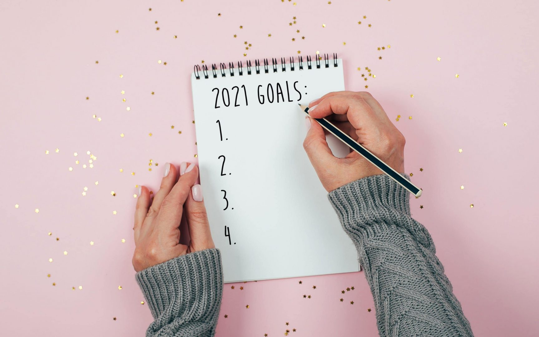 Happy New Year 2021. Woman's hand writing 2020 Goals in notebook decorated with Christmas decorations on the tricolor background. Top view, flat lay