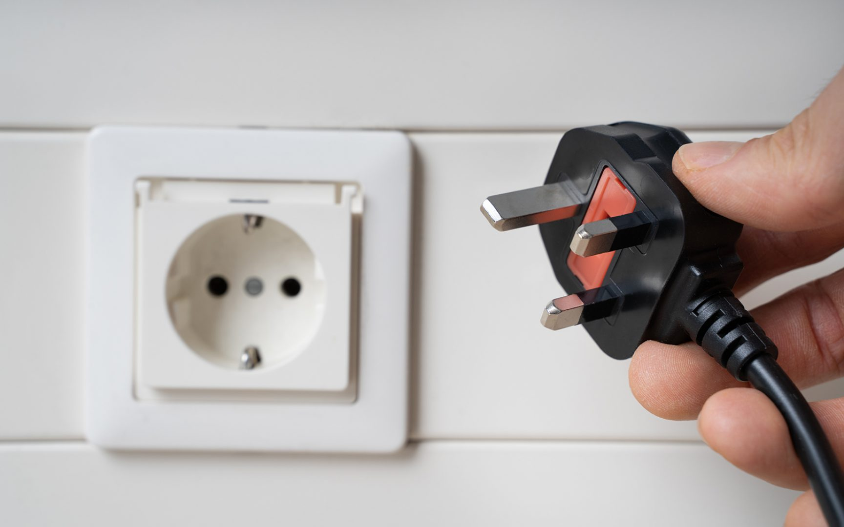 Hand Holding Incompatible AC Plug Near Wall Socket