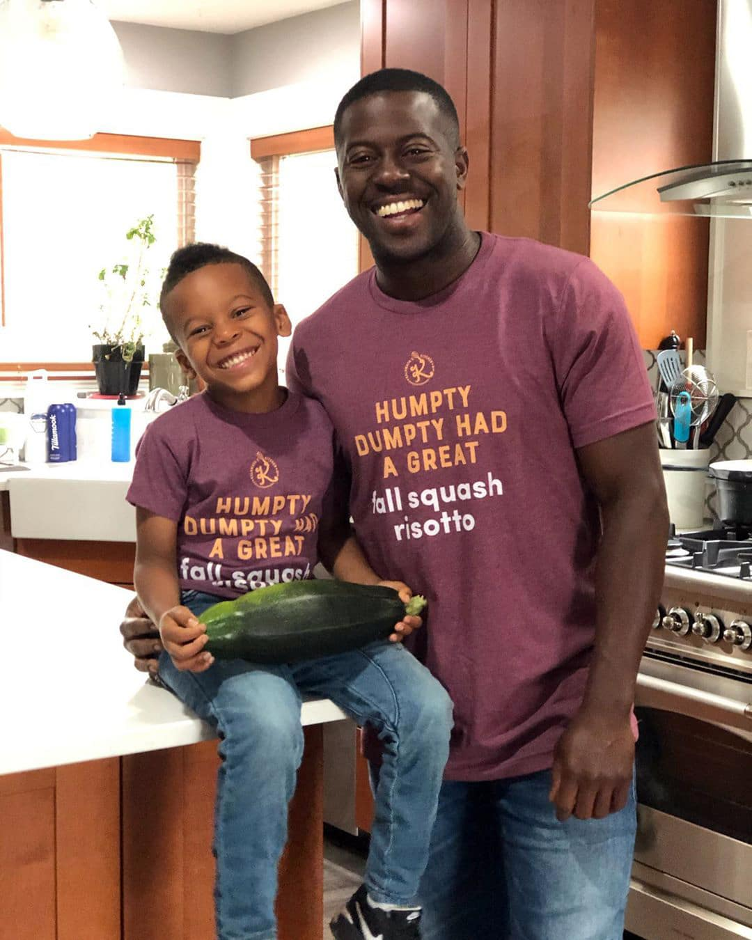 Edouardo Jordan and his son, Akil, pose for a photo in Jordan's kitchen. They wear matching shirts and Akil holds a large green vegetable.
