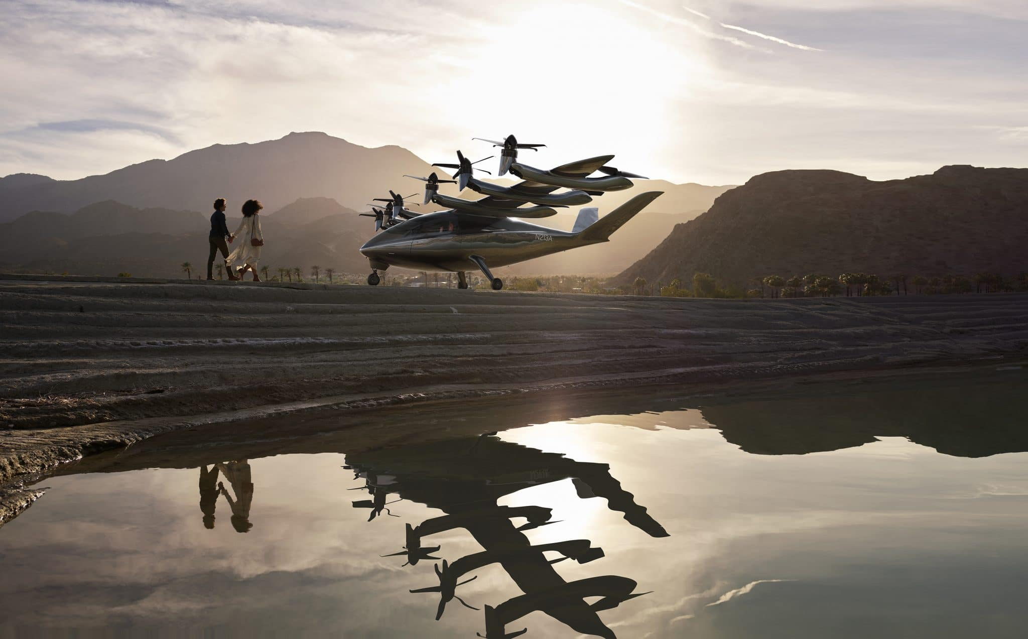 Small eVTOL landing in front of mountains. Two people stand in front.