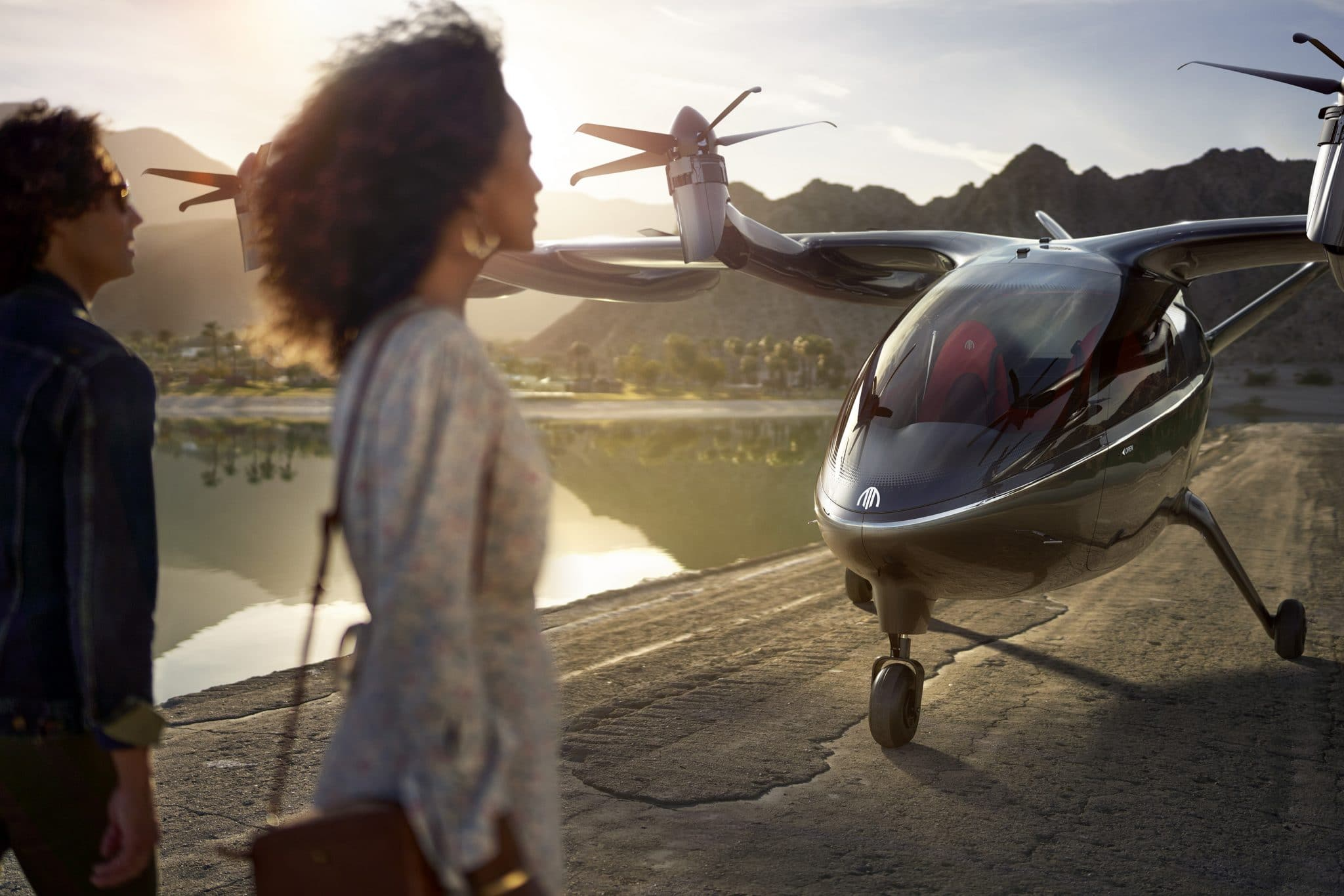 Two people standing in front of Archer's eVTOL.