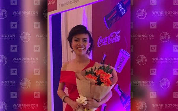 Nancy Tran holds a bouquet of flowers in front of a Coca-Cola step and repeat