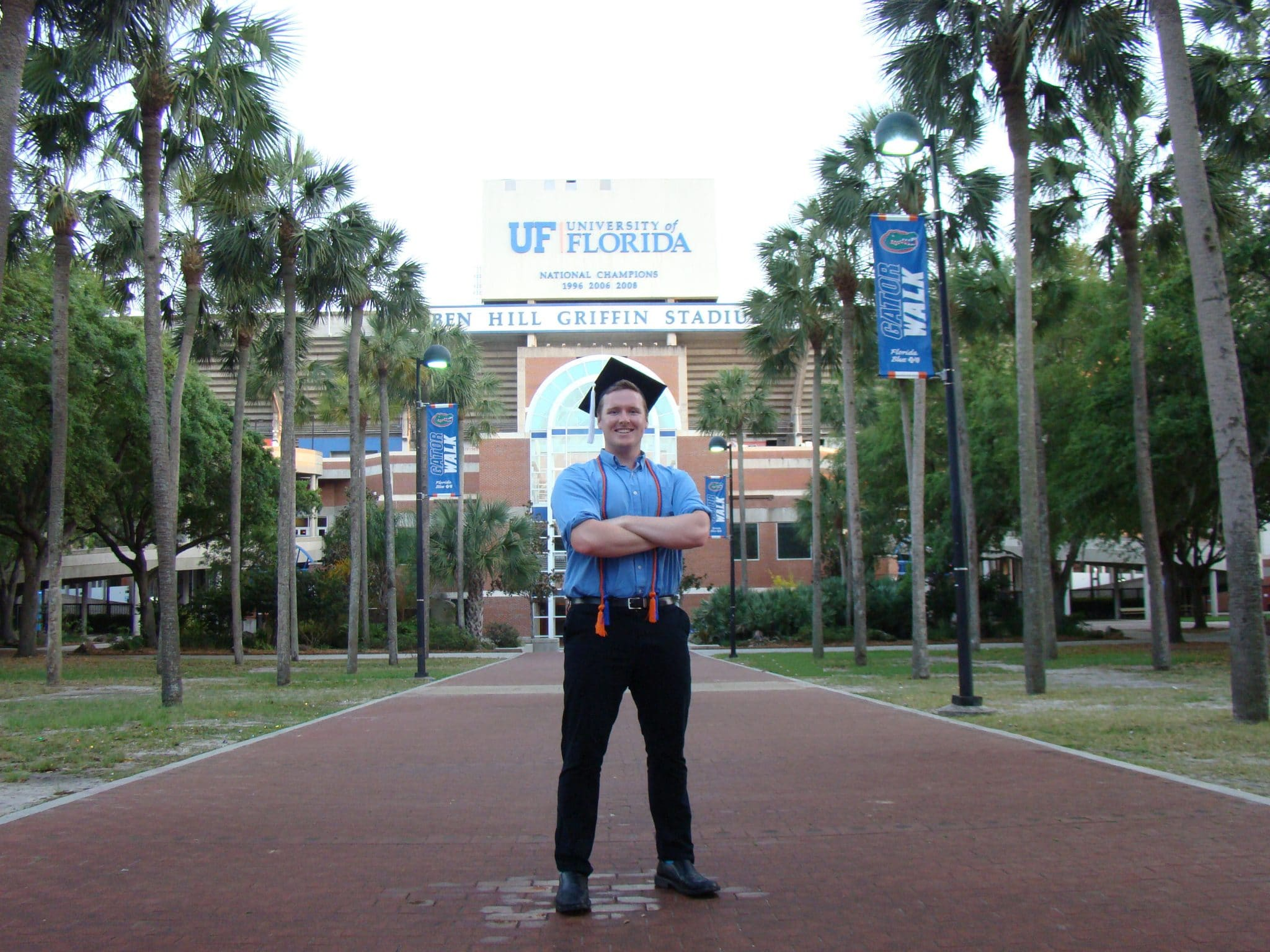 Jacob Schuster poses in his graduation cap in front of Ben Hill Griffin Stadium.