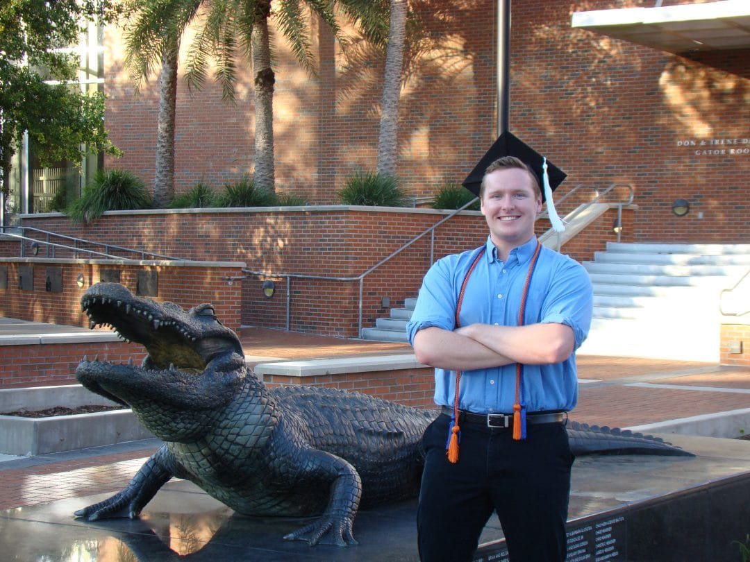 Jacob Schuster poses with his graduation cap next to an alligator statue.