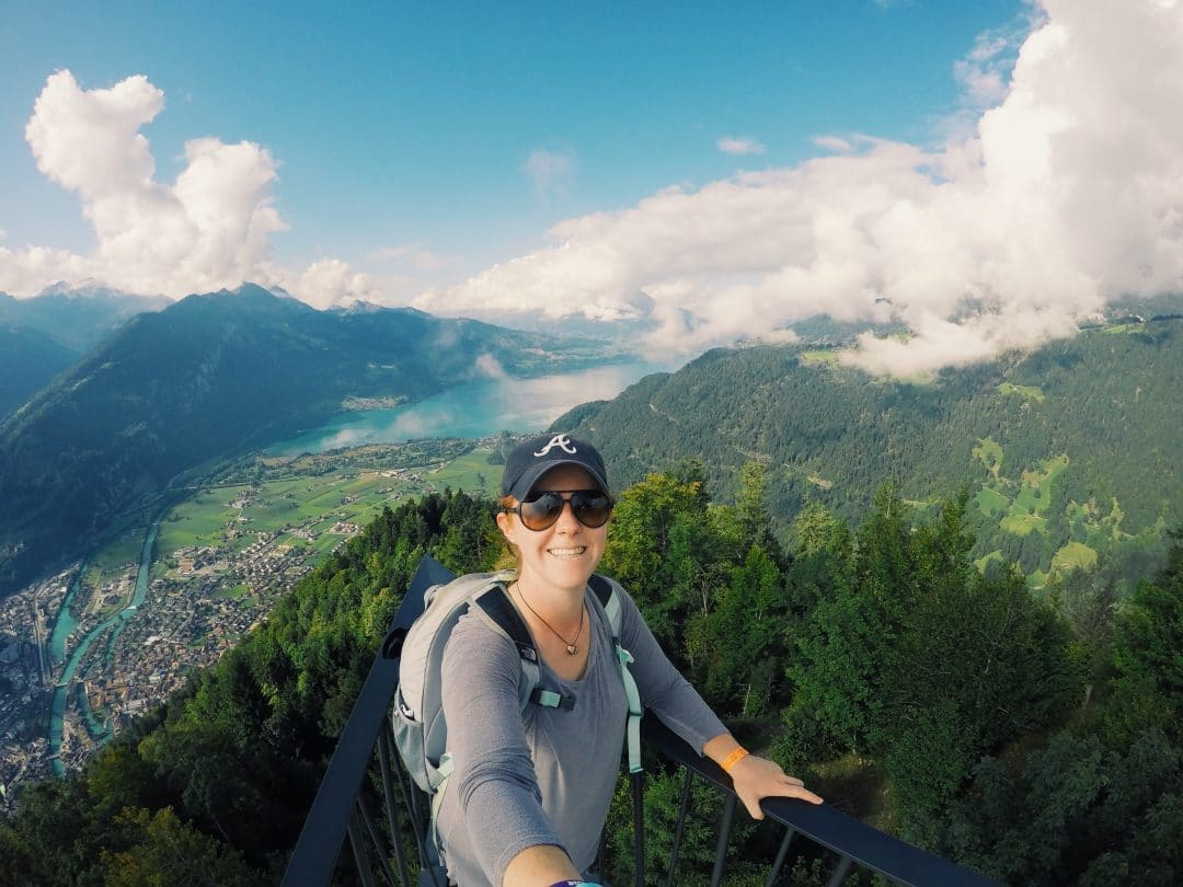 Stevie Faulk takes a photo with a selfie stick with the mountains of Switzerland in the background.