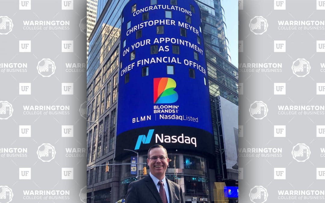 """Chris Meyer stands in front of a digital sign in New York City that reads 'Congratulations Christopher Meyer on your appointment as Chief Financial Officer"""" with the Blooming' Brands logo and NASDAQ logo."""