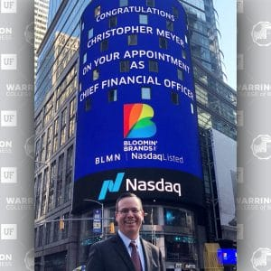 "Chris Meyer stands in front of a digital sign in New York City that reads 'Congratulations Christopher Meyer on your appointment as Chief Financial Officer"" with the Blooming' Brands logo and NASDAQ logo."