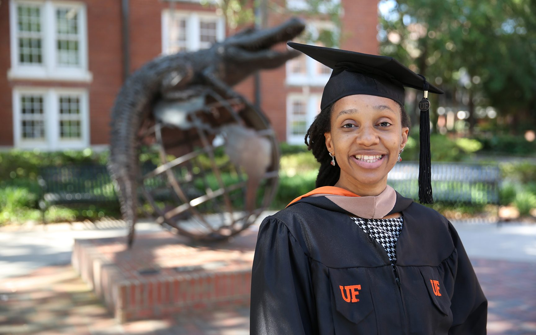 Erika Nang Sobze poses for a photo in her graduation cap and gown in front of the Gator Ubiquity Statue.