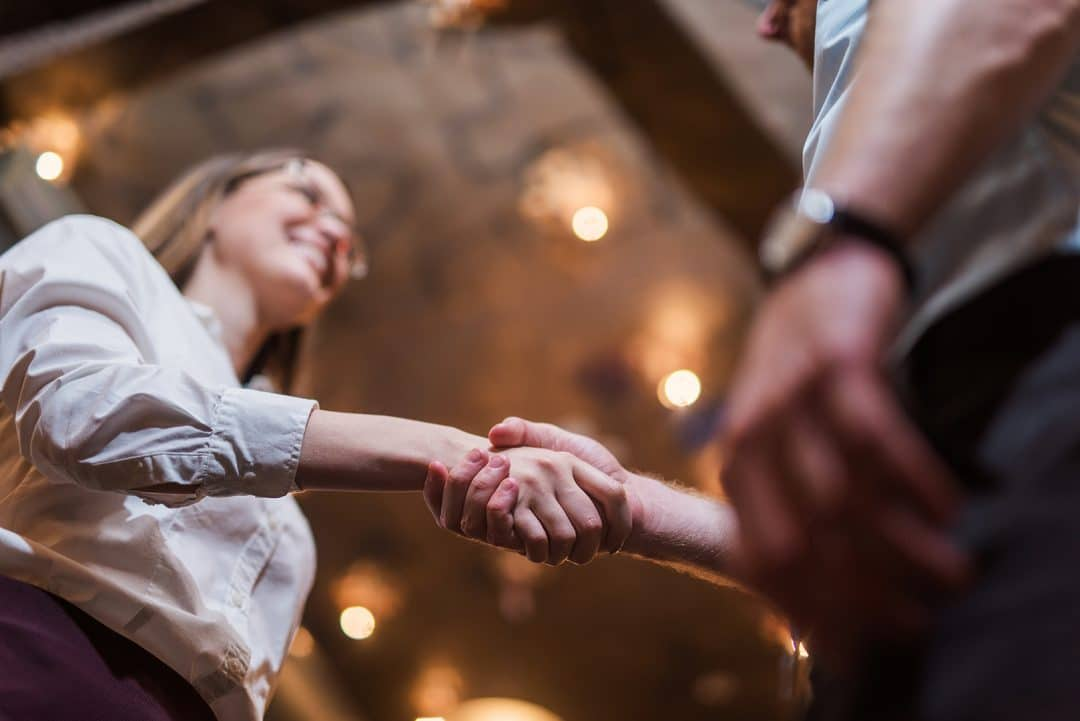 Photo from below of a young woman shaking hands with another person.