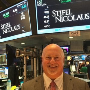 Ben Plotkin poses for a photo on the NYSE stock exchange floor under a sign with the Stifel trading price and analytics.