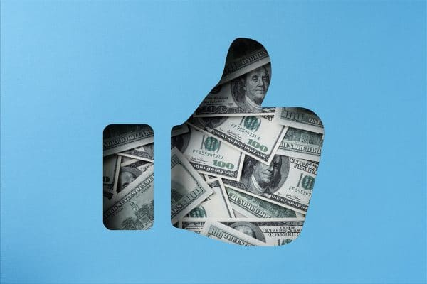 Money heap under paper cutout thumbs up icon, American one hundred dollar bill