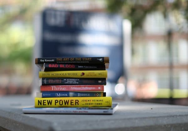 Stack of books on a picnic table in front of the Warrington College of Business sign.