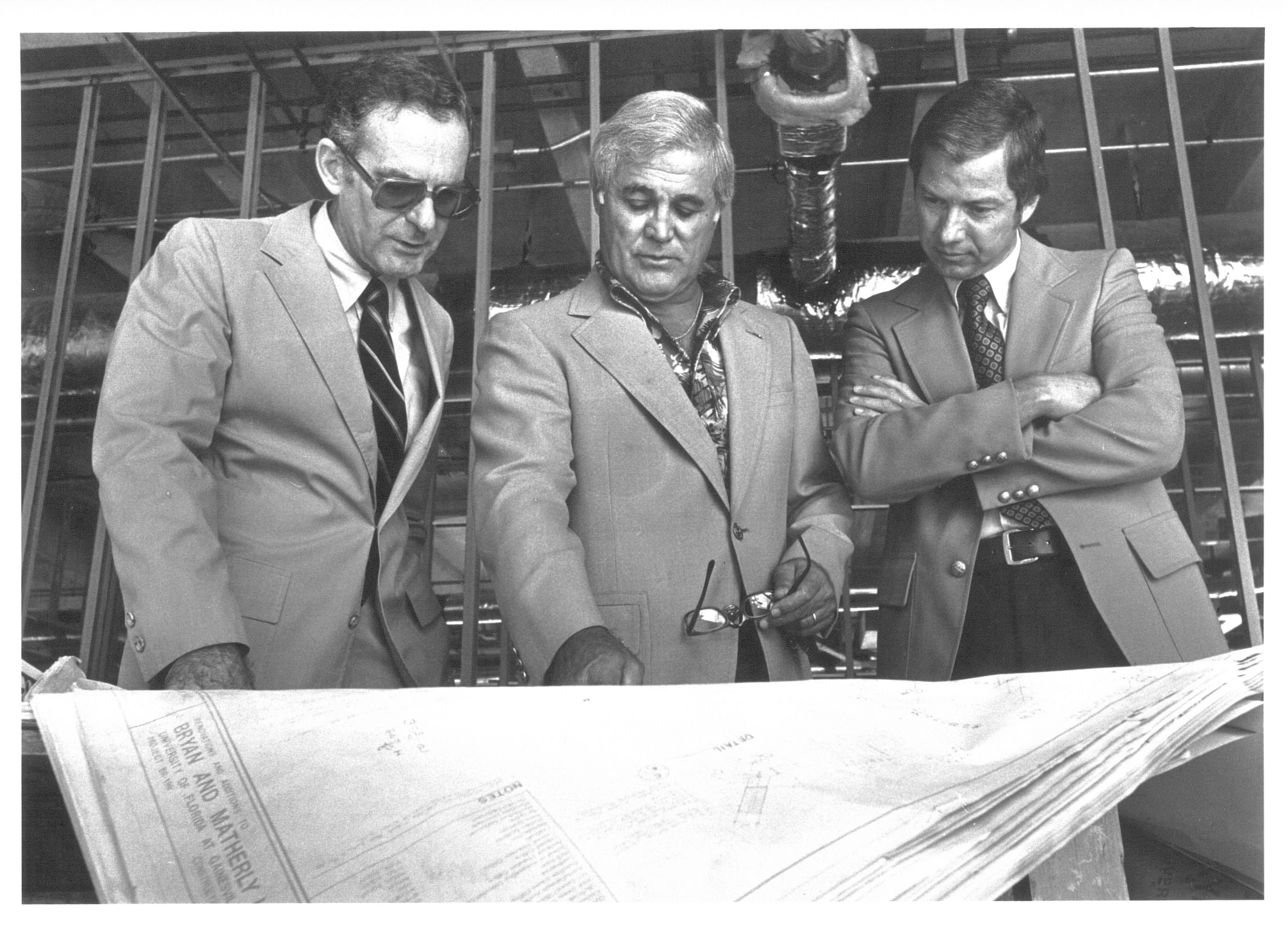 Hadley Schaefer, Robert Lanzillotti and John Simmons look down at plans for buildings on the Warrington College of Business campus.