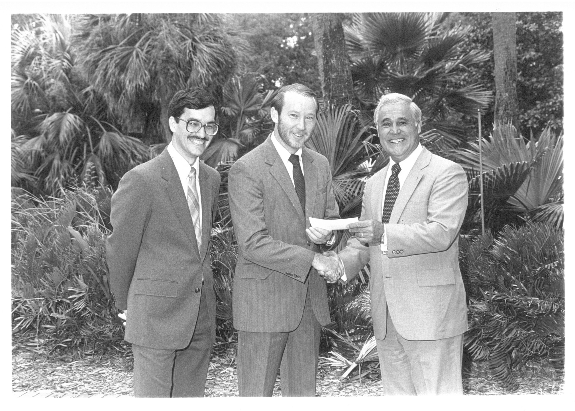 Two men pose for a photo with Robert Lanzillotti. One shakes Lanzillotti's hand while handing him a check.
